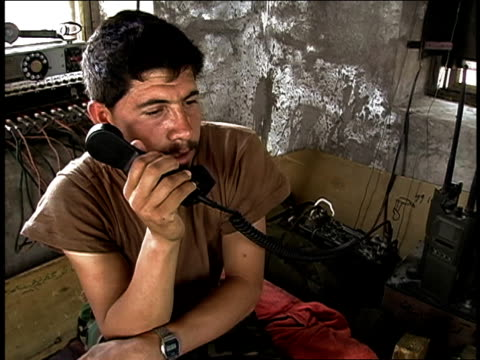 august 2004 medium shot afghan national army soldier talking on telephone/ afghanistan - operazione enduring freedom video stock e b–roll
