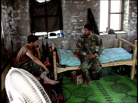 vídeos de stock, filmes e b-roll de august 2004 medium shot afghan national army soldier talking on telephone while another sits on cot/ afghanistan - household fixture