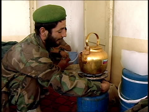 august 2004 medium shot afghan national army soldiers pouring water from pitcher and watching over kettle/ afghanistan - afghan national army stock videos & royalty-free footage
