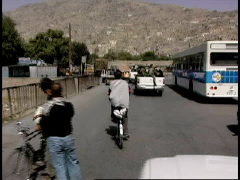 august 2004 medium shot afghan national army soldiers riding in pickup truck through traffic on crowded street/ afghanistan - personal land vehicle stock videos & royalty-free footage