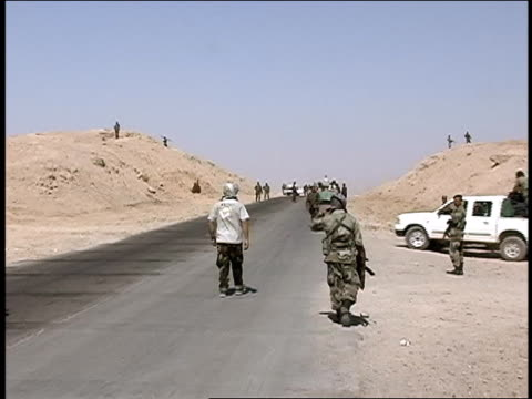 august 2004 medium shot afghan national army soldiers walking along road at checkpoint/ afghanistan - personal land vehicle stock videos & royalty-free footage