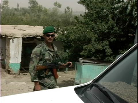 august 2004 medium shot afghan soldier with rifle standing guard outside shack / afghanistan - operazione enduring freedom video stock e b–roll