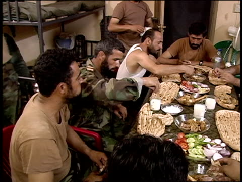August 2004 Medium shot Afghan soldiers eating meal around table/ Afghanistan