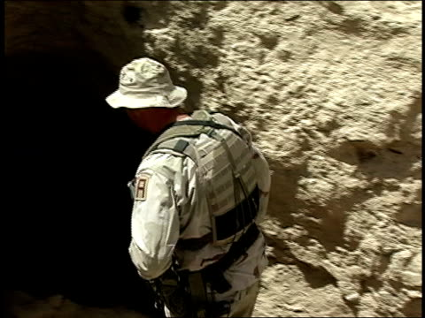 august 2004 medium shot american soldier looking into cave/ afghanistan - operazione enduring freedom video stock e b–roll