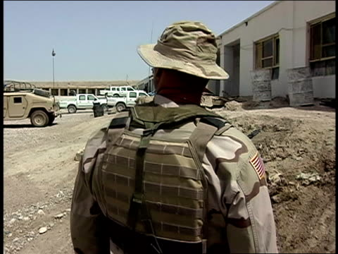 august 2004 medium shot american soldier standing outside army barracks/ afghanistan - operazione enduring freedom video stock e b–roll