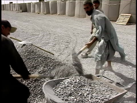 vidéos et rushes de august 2004 medium shot four afghan men shoveling gravel into wheelbarrow at construction site/ afghanistan - moins de 10 secondes