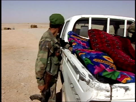 vidéos et rushes de august 2004 medium shot four afghan national army soldiers looking at colorful rugs in pickup truck/ afghanistan - moins de 10 secondes