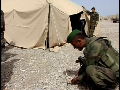 august 2004 medium shot four afghan national army soldiers pitching tent/ afghanistan - operazione enduring freedom video stock e b–roll