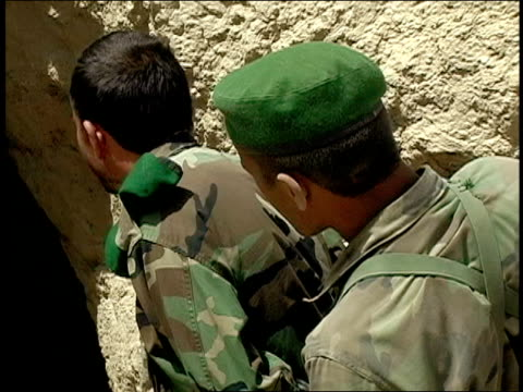 august 2004 medium shot high angle view american soldier entering and emerging from cave while two afghan national army soldier watch/ afghanistan - afghan national army stock videos & royalty-free footage