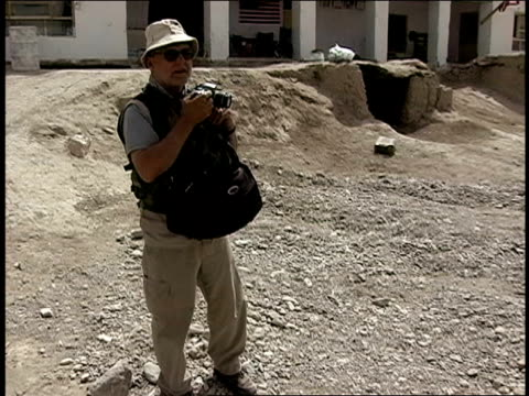 august 2004 medium shot high angle view photographer taking pictures outside building/ afghanistan - einzelner mann über 40 stock-videos und b-roll-filmmaterial