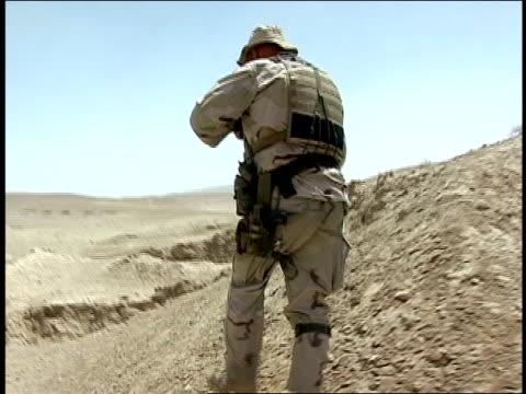 vídeos y material grabado en eventos de stock de august 2004 medium shot - low angle view american soldier walking over hill/ afghanistan - menos de diez segundos