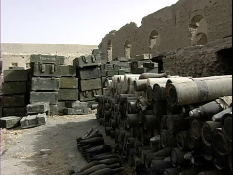 august 2004 medium shot piles of old missiles lying in stacks outside ruined building / afghanistan - operazione enduring freedom video stock e b–roll
