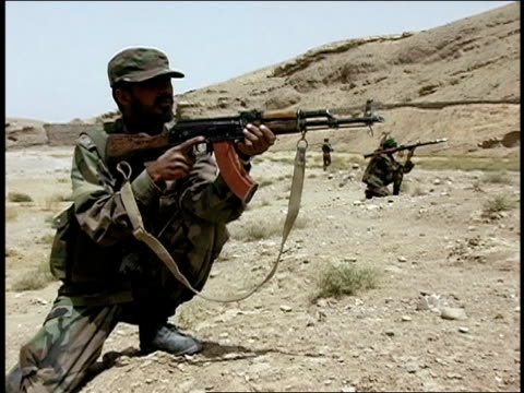 august 2004 medium shot three afghan national army soldiers aiming their rifles near hill/ afghanistan - operazione enduring freedom video stock e b–roll
