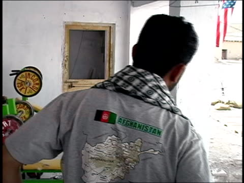 august 2004 medium shot two afghan national army soldiers in civilian clothes talking while one eats candy bar and the other stretches/ afghanistan - afghan national army stock videos & royalty-free footage