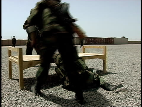 august 2004 medium shot two afghan national army soldiers searching another soldier after removing rifle during military training/ afghanistan - 仰向きに寝る点の映像素材/bロール