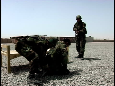 august 2004 medium shot two afghan national army soldiers taking another soldier prisoner during military training/ afghanistan - operazione enduring freedom video stock e b–roll