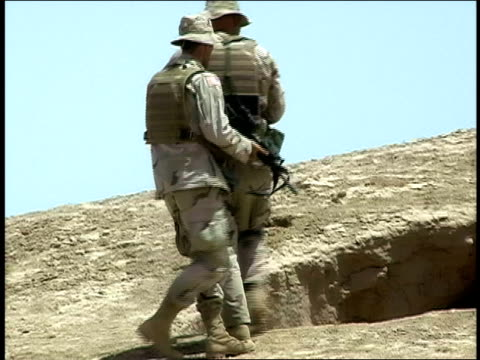 August 2004 Medium shot Two American soldiers aiming their rifles down hole in ground while Afghan man watches/ Afghanistan