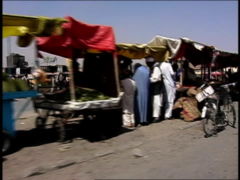 vídeos y material grabado en eventos de stock de august 2004 tracking shot pedestrians walking along city street crowded with traffic and outdoor market/ afghanistan - menos de diez segundos