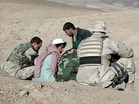 August 2004 Wide shot Afghan and US soldiers talking to prisoner in desert/ Afghanistan