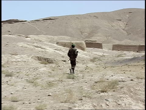 august 2004 wide shot afghan national army soldier walking with rifle/ afghanistan - afghan national army stock videos & royalty-free footage