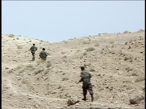 august 2004 wide shot four afghan national army soldiers running up hill/ afghanistan - afghanische nationaltruppe stock-videos und b-roll-filmmaterial