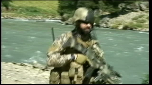 helmand province general views of us army base us troops on patrol alongside river as taliban and us gunfire seen and heard in surrounding hills sot... - army soldier stock videos & royalty-free footage