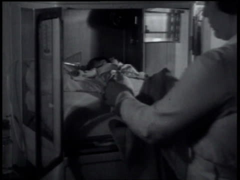 August 24, 1934 MONTAGE Woman opens incubator with premature baby inside and takes holds, then weighs as people look from behind glass