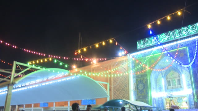 stockvideo's en b-roll-footage met august 26 2010 td brightly colored lights hanging from buildings as pedestrians walk across square / najaf iraq - najaf