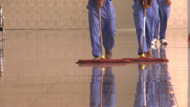 august 26 2010 tu cleaning crew sweeping the floor at mirage mall / najaf iraq - najaf stock-videos und b-roll-filmmaterial