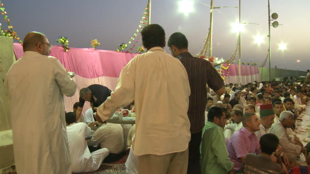 vídeos de stock, filmes e b-roll de august 26 2010 pan crowd of diners seated on the ground at long tables while servers with trays pass out food at the close of ramadan / najaf iraq - 2010