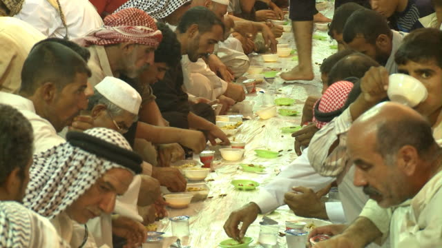 august 26, 2010 crowd of diners seated on the ground at long tables eating food with their hands at the close of ramadan / najaf, iraq - najaf stock videos & royalty-free footage