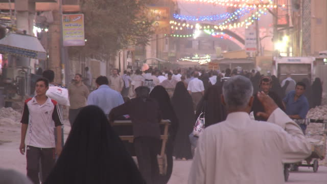 stockvideo's en b-roll-footage met august 26 2010 ha crowded street scene of pedestrians and vendors pushing carts with string lights hanging over the street / najaf iraq - najaf