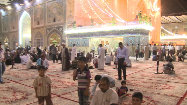 august 26 2010 pan crowds of festival goers congregating praying sitting and waiting in shrine at the close of ramadan / najaf iraq - najaf stock-videos und b-roll-filmmaterial