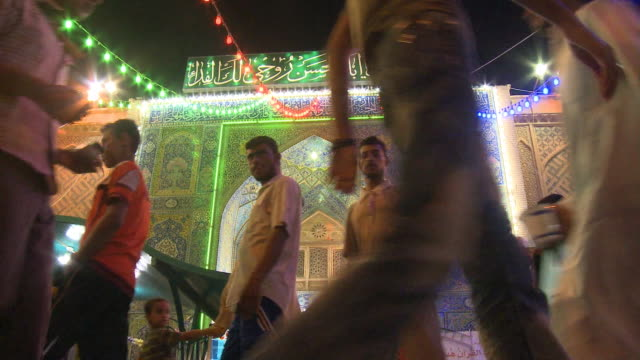 august 26, 2010 facade of brightly lit archway of multi-colored tiles as pedestrians pass at the close of ramadan / najaf, iraq - najaf stock videos & royalty-free footage