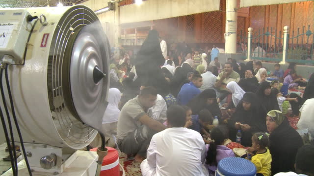 vídeos y material grabado en eventos de stock de august 26 2010 ha fan blowing on crowd of diners seated on the ground at long tables eating at close of ramadan / najaf iraq - najaf