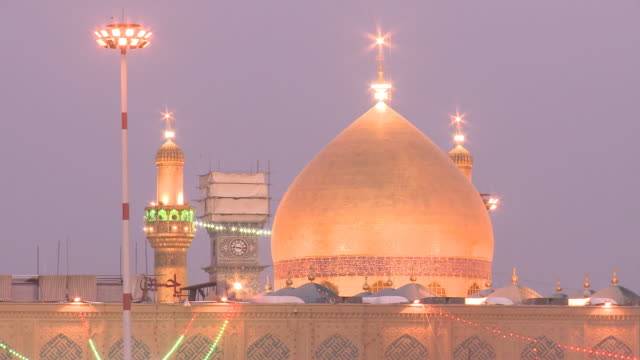 august 26, 2010 golden dome and spires of imam ali mosque lit up at dusk / najaf, iraq - shrine of the imam ali ibn abi talib stock videos & royalty-free footage