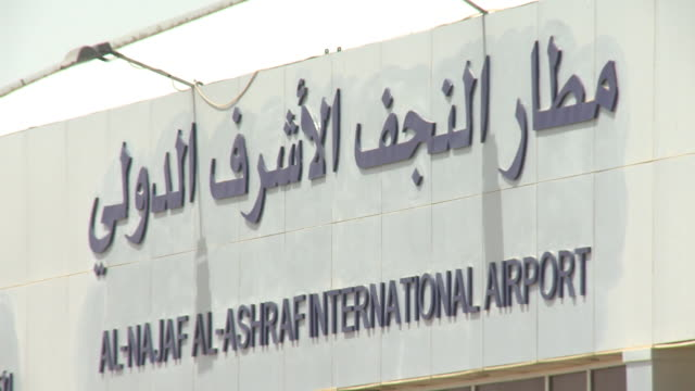 august 26 2010 montage exterior sign for najaf international airport and luggage trolleys outside the terminal / najaf iraq - najaf stock-videos und b-roll-filmmaterial