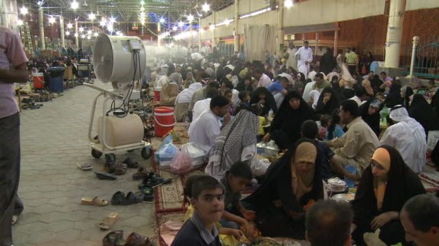 august 26, 2010 montage fan blows on crowd of diners seated on the ground at long tables eating at close of ramadan / najaf, iraq - najaf stock videos & royalty-free footage