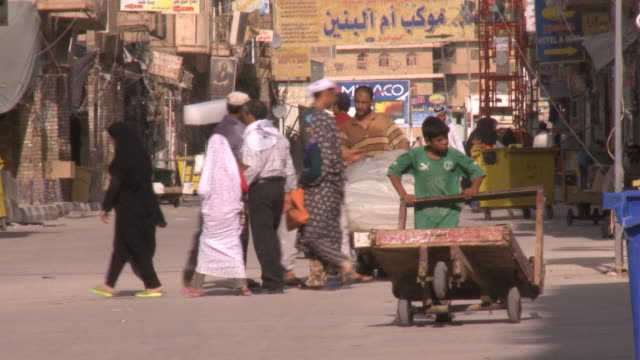 august 26, 2010 montage street scenes of vendors pushing carts, pedestrians walking and congregating / najaf, iraq - najaf stock videos & royalty-free footage