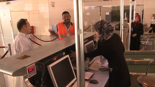 august 26 2010 ha passenger speaking to ticket agent at najaf international airport / najaf iraq - najaf stock-videos und b-roll-filmmaterial