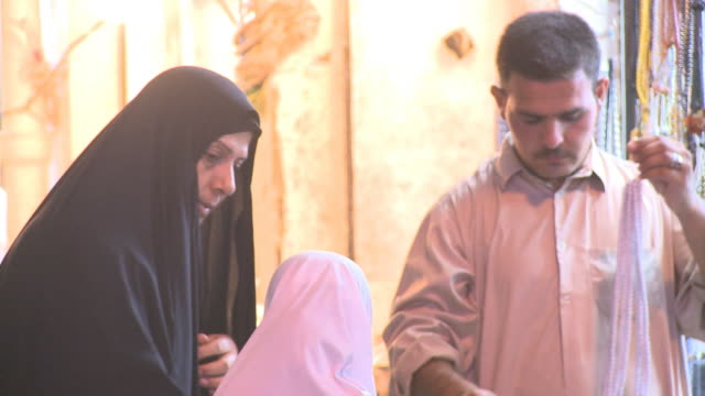 stockvideo's en b-roll-footage met august 26 2010 pan shopper purchasing necklace for her daughter at outdoor market / najaf iraq - najaf