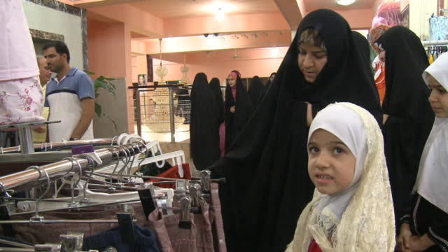 august 26, 2010 shoppers browsing racks of clothing at the mirage mall / najaf, iraq - najaf stock videos & royalty-free footage