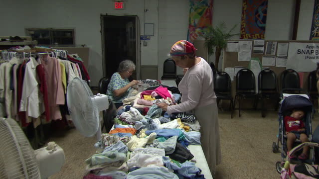 august 26 2010 zi volunteers sorting through clothing inside community center / louisiana united states - community centre stock videos & royalty-free footage