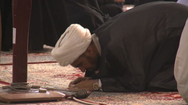 august 26, 2010 worshiper bowing and praying on carpeted floor with pedestrians milling about imam ali mosque / najaf, iraq - shrine of the imam ali ibn abi talib stock videos & royalty-free footage