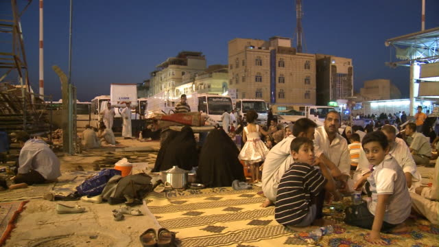 august 26 2010 pan worshipers sitting on blankets outside the imam ali mosque / najaf iraq - najaf stock-videos und b-roll-filmmaterial