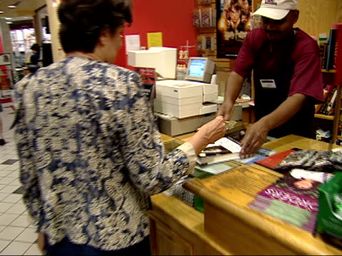 august 27, 2002 shopper buying a book at a borders bookstore / united states - ボーダーズ・ブックス点の映像素材/bロール