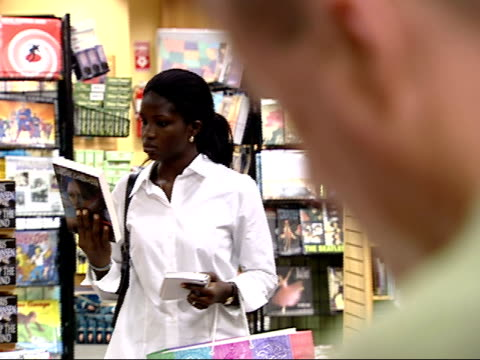 august 27, 2002 shopper looking at a book at a borders bookstore / united states - ボーダーズ・ブックス点の映像素材/bロール