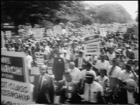 b/w august 28 1963 high angle large crowd with signs marching on wide street / march on washington / newsreel - marciare video stock e b–roll