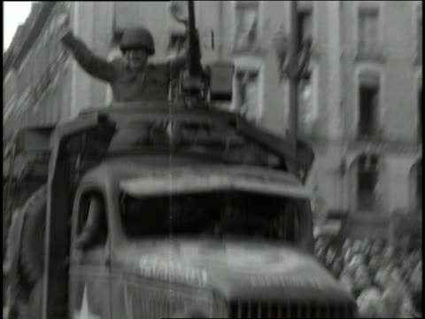 august 4 1944 ws french civilians waving american flags at soldiers passing in jeeps and trucks during wwii / rennes france - rennes frankreich stock-videos und b-roll-filmmaterial