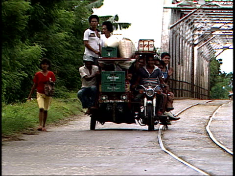 august 4, 1985 four passengers and a lot of baggage riding on a motorcycle sidecar down a street / philippines - sidecar stock videos & royalty-free footage